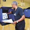 Charles Walker puts the voting instructions inside each of the voting booths at his precinct at Union 9 at Bethany Christian Church Monday evening as he and the other poll workers setup their precinct for election day.