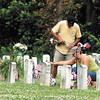 Cathy Gray visits her father's grave at Maplewood Cemetery as her husband Ted puts flowers in a water container to place on the site Memorial Day afternoon.