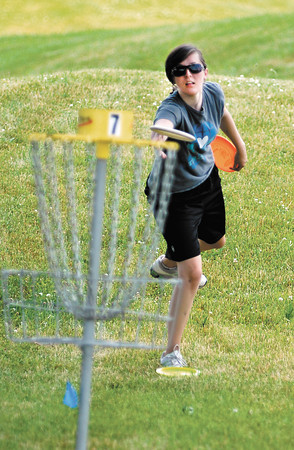 Brenna Sterken plays disc golf at a temporary course setup in Pulaski Park in Anderson Saturday as part of a fundraiser to help raise money to build a permanent course at the park.