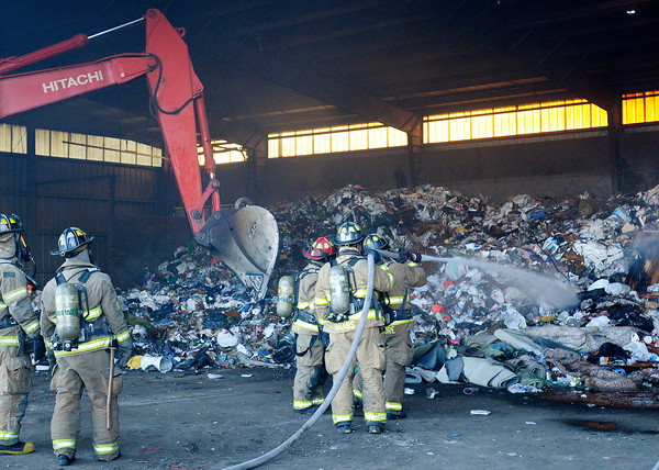 An excavator moves around garbage as Anderson fire fighters search for hot spots after extinguishing a trash fire at Best Way Disposal's transfer station on Madison Avenue on Wednesday.