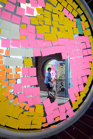 The mail lady enters Anderson High School  Friday morning through a maze of Post-It notes that covered most all the windows as part of a senior class prank overnight.