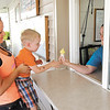 Abram Abshire, 2, gets a boost from his mom Katie as Allyssa Sullivan hands him his ice cream cone at Dor-Tee's Drive-In in Alexandria.