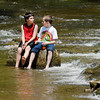 Friends Zachary Picco, 11, and Noah Imel, 11, found a good way to keep cool Wednesday afternoon as the temperatures started to warm up by sitting on a large rock in the middle of Fall Creek in Pendleton and dangling their feet in the moving water.  The neighbor boys, out on their first week of summer vacation, were having fun spending time together.
