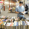Christopher Pine looks over a table of books during the Friends of the Library book sale on Friday. The floor space for the Friends of the Library book sale will be reduced after renovations to add a meeting room are complete.