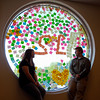 AHS's seniors Adriene Hendricks and Brandon Heath sit in one of the windows of the school Friday morning that was totally covered with Post-It notes as part of a senior class prank overnight.