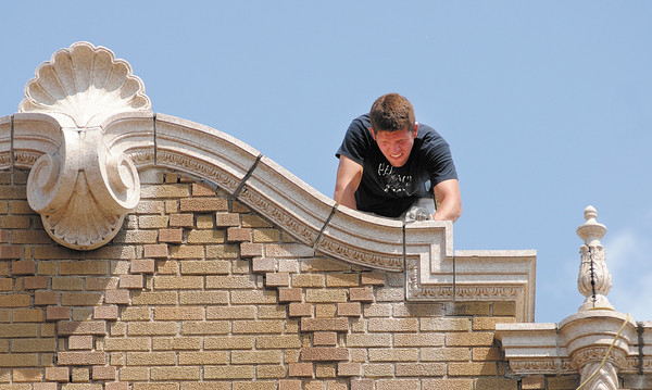 Workers repair the mortar joints on the Paramount on Monday.