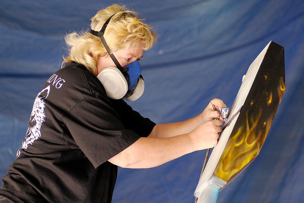 Wendy Otto of Twin Airbrushing woks on a Walking Man sculpture sponsored by Mofab. The sculptures will be on display around the city from June through September.