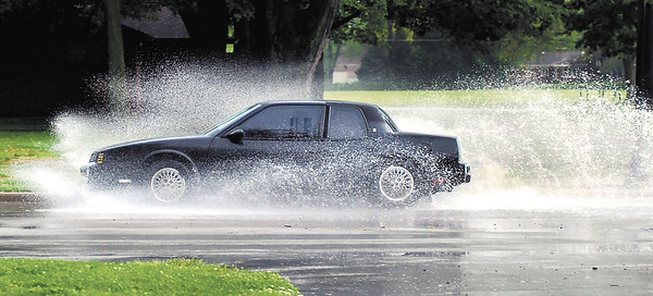 Vehicles drive through high water along University Blvd. after heavy rains fell Tuesday afternoon over the area.