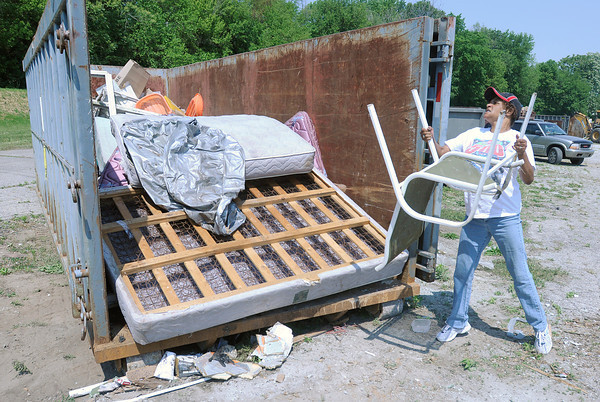 Ruth Hester tosses a chair into a dumpster as residents dump truck and trailer loads of garbage into dumpsters at Athletic Park during the city's annual cleanup on Saturday.