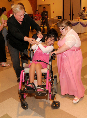 From left, Jennifer Baylor, Susanna Ginder and Logan Grim dance during a prom for special needs students from Pendleton Heights High School and Anderson High School at SonRise Ministries in Anderson.