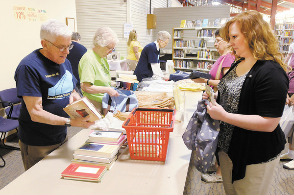 Curt McGuire tallies the total price for books picked out by Dana Shepherd during the Friends of the Library Book Sale on Friday. The floor space for the Friends of the Library book sale will be reduced after renovations to add a meeting room are complete.