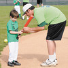Brandon Schnepp gives Connor Partain some batting pointers as Champions baseball plays at Pendleton Heights' Legends Field on Saturday.
