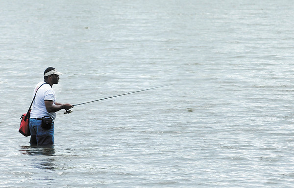 A fisherman wades out into the lake at Shadyside to try his luck during unseasonably warm weather Wednesday afternoon.