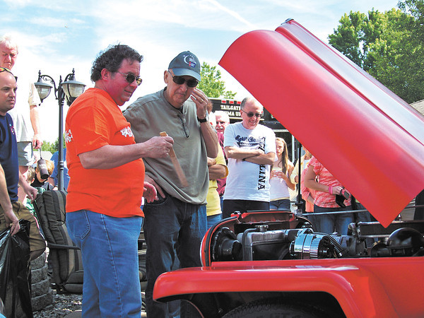 Steve Holt wipes away a tear as Steve Griffith shows him the rebuilt engine in his 1948 Willys Jeep Delivery Sedan.