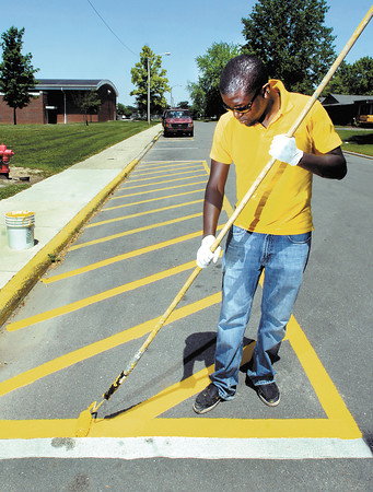 Raymond Litondo works his way down Graceland Ave. Wednesday as he was painting the parking stripes along the street.  Litondo works for the university's physical  plant as they prepare the campus for the different summer activities that they host.
