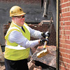 Director of Municipal Development for the city of Anderson, Frank Owens, gives the wall of the old Emge building a ceremonial whack with a sledge hammer as demolition started Monday on the vacant structure.