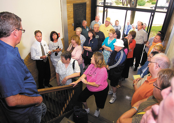 Joe Buck, second from left,  South Madison Schools Superintendent, answers questions from those gathered at the old high school building to take a tour of the 1936 facility.