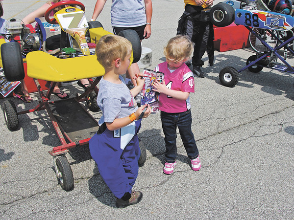 """Four year old Kart driver Palmer """"P. J."""" Eicher of Noblesville, Indiana signing an autograph for a fan."""