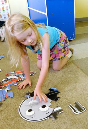 Savannah Hudson, 5, assembles a  Thomas the Train puzzle at the Gateway Association  inside First United Methodist Church on Tuesday.