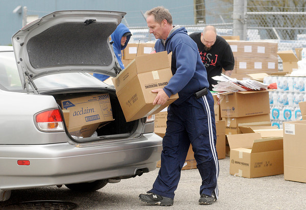 Tony Shelton loads a box into a car as he volunteers during a giveway by the Elwood Mission at the Tops True Value in Elwood on Saturday.