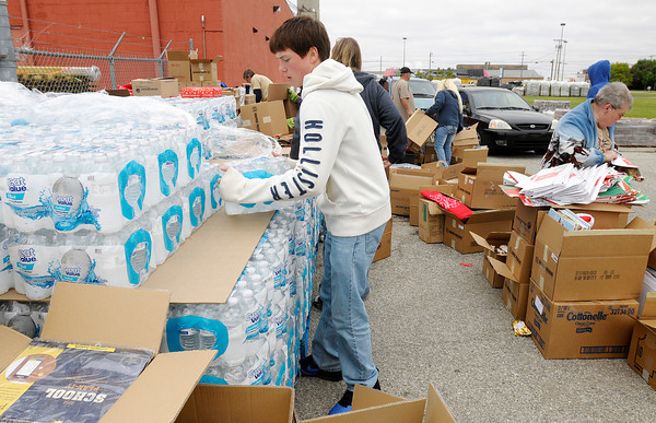 Jake Mahuney distributes cases of water during a give away by the Elwood Mission at the Tops True Value in Elwood on Saturday.