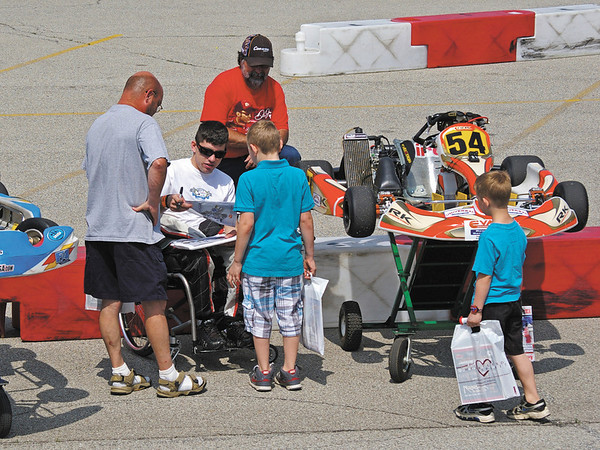 Paraplegic Kart driver Michael Johnson of Mount Morris, Michigan sings autographs.  As well as Karts, this year Michael is driving a Formula 2000 car in the Mazda Road to Indy Series.