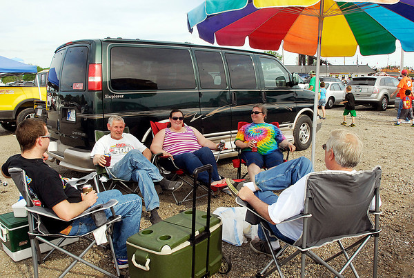 John P. Cleary / The Herald Bulletin<br /> Ethan Bergman, Dave Fisher, Mary Bergman, Pat Bergman, and Larry Bergman, all from Ft. Wayne, enjoy the weather under their patio umbrella in the parking lot of Anderson Speedway before the start of the Little 500 Saturday evening.  This is Fishers 30th Little 500 and Pat Bergman's first race.