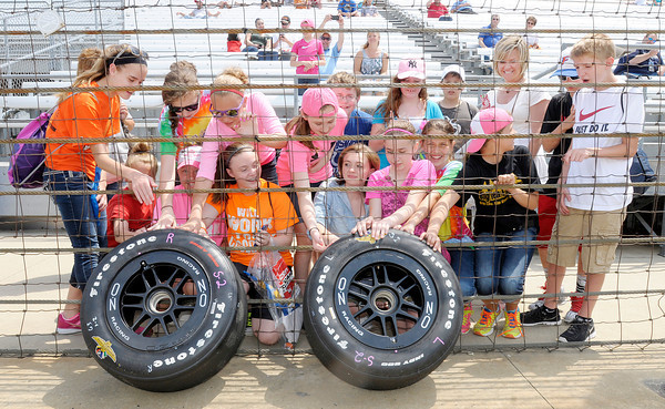 Don Knight | The Herald Bulletin<br /> Pippa Mann fans touch a pair of tires still warm from practice laps at the Indianapolis Motor Speedway on Tuesday. Heavy rain cut the day's practice short.