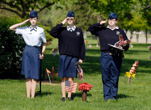 John P. Cleary   The Herald Bulletin<br /> Cadets Megan Simmet, Victoria Morea, and Shyanne Bryant salute after placing an American flag on this veterans' grave in Anderson Memorial Park Monday morning.  Anderson Preparatory Academy students are spending three days placing the flags on the graves of deceased members of the military.