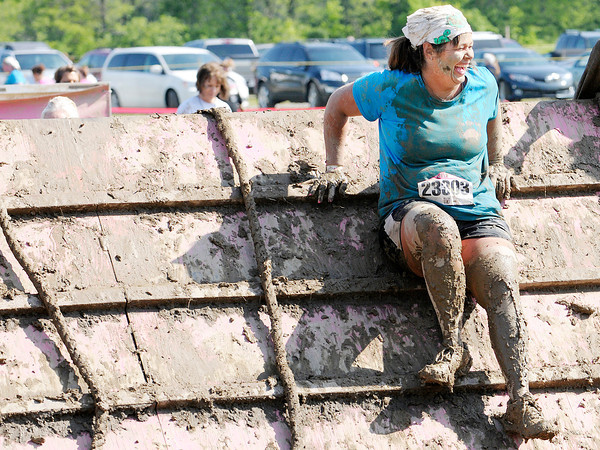 Don Knight | The Herald Bulletin<br /> A participant smiles after climbing over an obstacle during the Dirty Girl 5K Mud Run at White River Paintball on Saturday. To view or buy this photo and other Herald Bulletin photos, visit heraldbulletin.smugmug.com.