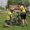 While stopped at Good's Candy Shop, Jimmy Dallas adjusts the rear wheel on Toni Harris's bike during the Anderson CycloFemme Mother's Day event.