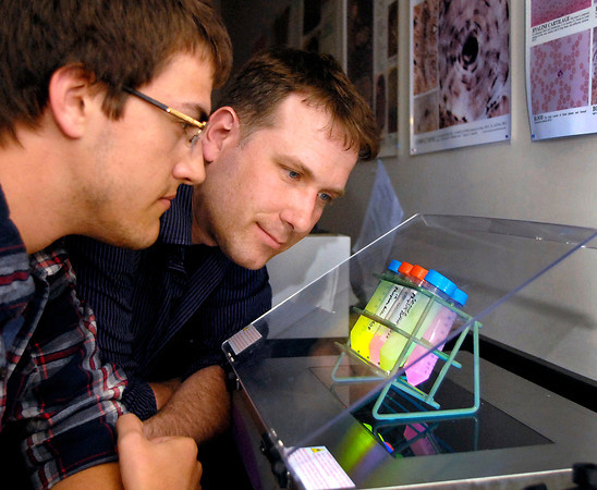 John P. Cleary | The Herald Bulletin<br /> Anderson University junior Ethan Hillman and his his professor Scott Kennedy look over some of the different samples of luminescent hydrogels that Kennedy has been doing research on for the U.S. Air Force in the AU labs. The goal of the research is to have the substance detect minute quantities of explosives. Kennedy is spending his summer doing research for Google X.