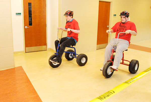 Don Knight | The Herald Bulletin<br /> From left, Devin Humphrey and Zachary Saylor race on a pair of giant tricycles during Student Appreciation Day at Anderson High School on Friday. To view or buy this photo and other Herald Bulletin photos, visit heraldbulletin.smugmug.com.