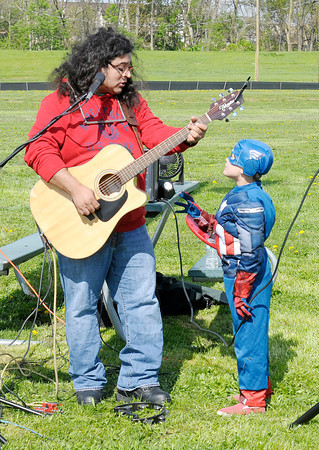 Don Knight | The Herald Bulletin<br /> Local musician JT Sifuentes talks to his son Josiah, 9, as Anderson's City Market opened on Saturday at Athletic Park. Sifuentes was performing and brought his son along who dressed in his Captain America costume. To view or buy this photo and other Herald Bulletin photos, visit heraldbulletin.smugmug.com.
