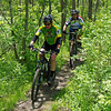 Mountian bikers ride along a narrow trail in the Rangeline Nature Preserve.
