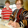 "John P. Cleary | The Herald Bulletin<br /> Former teacher Linda Robbins signs the first copy of her book ""Mrs. Robbins' Ducky Day"" for former student Charlie Dubree, 12, who urged her to write the book."