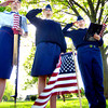 John P. Cleary | The Herald Bulletin<br /> Cadets Megan Simmet, Victoria Morea, and Shyanne Bryant salute after placing an American flag on this veterans' grave in Anderson Memorial Park Monday morning.  Anderson Preparatory Academy students are spending three days placing the flags on the graves of deceased members of the military.