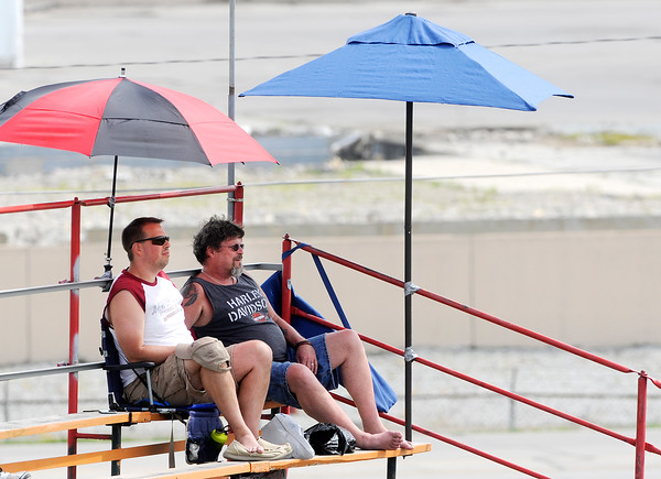Don Knight | The Herald Bulletin<br /> These two sprint car fans sit under umbrellas at the Anderson Speedway while watching drivers qualify for the Little 500 on Thursday. Qualifying was delayed two hours due to rain.