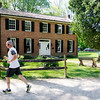 Don Knight | The Herald Bulletin<br /> A jogger runs past the  Bronnenberg Home at Mounds State Park. The Friends of Mounds State Park are hosting an open house today (Saturday) from 1 to 4 p.m.