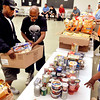 John P. Cleary | The Herald Bulletin<br /> Volunteer Terry Hyatt carries the box for Willie Christian as he selects food items while going through the Carrie M. Hyatt food pantry.