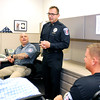 John P. Cleary | The Herald Bulletin<br /> Anderson Police Chief Tony Watters, standing, talks with detective Mark Brizendine, K-9 officer Marty Dulworth, and officer Bret Webb in the Community Policing office of headquarters.