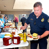 John P. Cleary | for The Herald Bulletin<br /> Corrections officer Pat Gibson loads up his sandwiches with condiments during a cookout Thursday at the Pendleton Correctional Industrial Facility during activities for their celebration of  National Correction Employees Appreciation Week.
