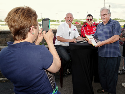 Mark Maynard | For The Herald Bulletin Laura Wilson of Alexandria snaps a picture of her husband, Mike, with Bobby and Graham Rahal during an autograph session presented by Budweiser at Hoosier Park.