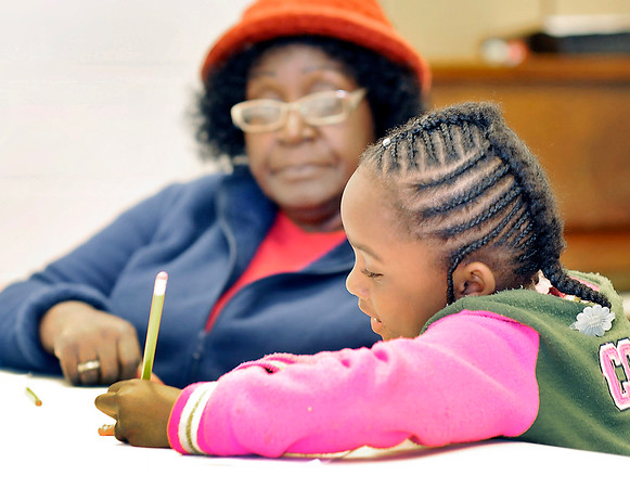 John P. Cleary |  The Herald Bulletin<br /> Zaviaye English, 6, Works on her schoolwork as volunteer Corrine Rolling looks on as she helps tutor students after school at the Trustee Girls and Boys Club.