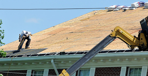 John P. Cleary |  The Herald Bulletin<br /> This worker holds on to his rope as he secures a section of roofing at Myers Residence Hall on the Anderson University campus Thursday. Fredericks Inc., of Pendleton, is putting on a new roof on the dorm building.
