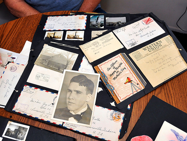John P. Cleary |  The Herald Bulletin<br /> Greg Frolke goes over photos and letters belonging to his father Darrell Frolke, pictured, during WWII that Richard Petty got from an old storage locker he bought at auction than tracked down the family.