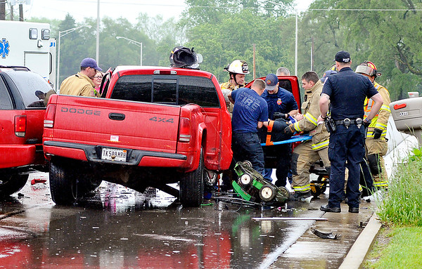 John P. Cleary    The Herald Bulletin<br /> Anderson Fire Department medic and rescue personnel work to extract a person from this truck that was involved in a two-vehicle accident on MLK Blvd. and Bent Grass Drive Thursday morning.