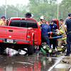 John P. Cleary |  The Herald Bulletin<br /> Anderson Fire Department medic and rescue personnel work to extract a person from this truck that was involved in a two-vehicle accident on MLK Blvd. and Bent Grass Drive Thursday morning.