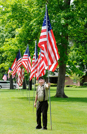 Don Knight   The Herald Bulletin<br /> Grounds keeper John Modlin adjusts a flag as Modlin, Joshua Shepler and Keith Sherman put out flags at Maplewood Cemetery ahead of the Memorial Day Weekend. Several flags will come down after the holiday but the ones lining the drive between the main entrance and the veterans section will remain up until after Flag Day in June.