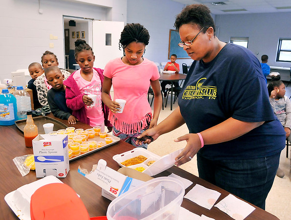 John P. Cleary |  The Herald Bulletin<br /> Trustee Girls and Boys Club staff member Porschea Maxwell, right, hands out ravioli meals to waiting kids at the facility this past week after school.